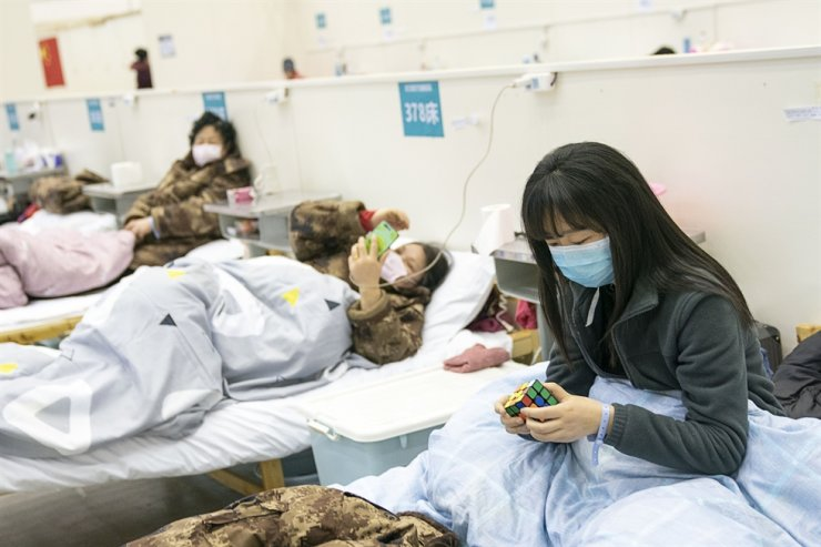 A patient solves a Rubik's cube at a temporary hospital in Wuhan, in central China's Hubei Province, Feb. 10. Xinhua-Yonhap