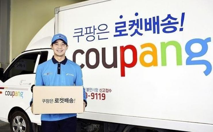 Coupang deliveryman pose for picture in this 2016 file photo. / Courtesy of Coupang
