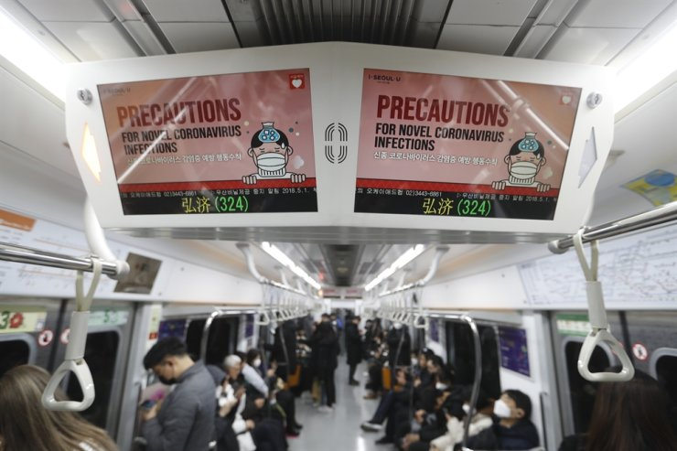 Electric screens about precautions against the illness COVID-19 are seen in a subway train in Seoul, Monday, Feb. 17, 2020. AP
