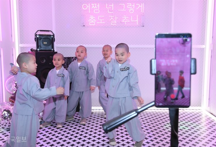 Young monks try on 5G-based AR and VR service of LG Uplus at the mobile carrier's store in Seoul, May 7, 2019. / Korea Times file