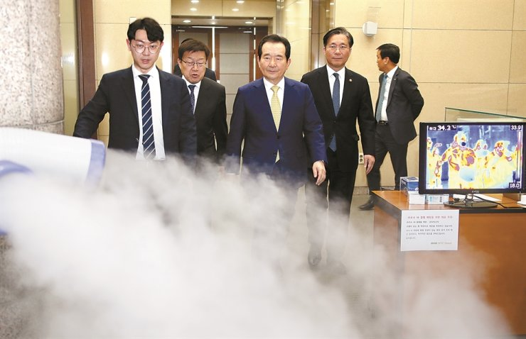 Prime Minister Chung Sye-kyun passes through disinfectant, intended to prevent the spread of 2019-nCoV (COVID-19), to attend a joint meeting of executives from the public and private sectors on trade strategy held at the Trade Tower in Gangnam, southern Seoul, Thursday. Yonhap