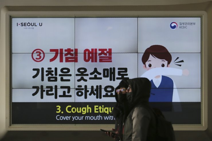 People wearing face masks pass by an electric screen about precautions against the illness COVID-19 in Seoul, Tuesday, Feb. 18, 2020. AP