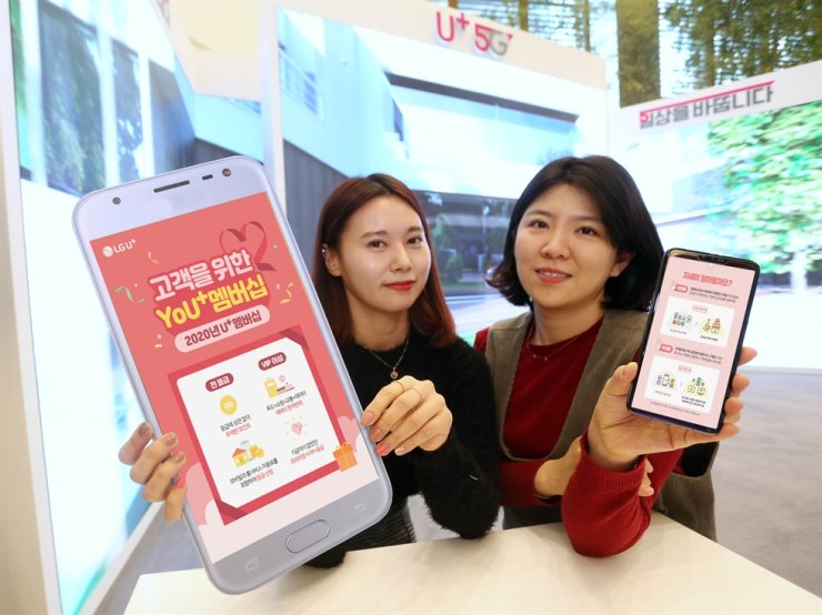 Models hold up smartphone shaped signs to promote LG U+'s unlimited membership points service. Telecom companies have been criticized for reducing regular customer benefits to increase perks for VIPs and VVIPs. Courtesy of LG Uplus