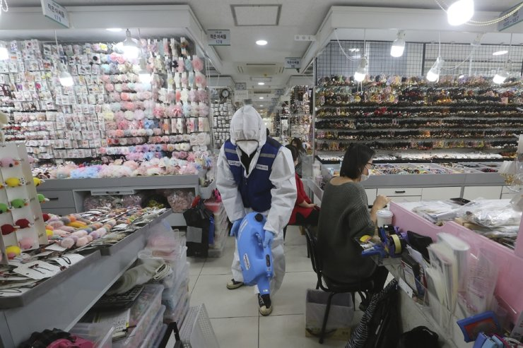A worker wearing protective gears sprays disinfectant inside a store as a precaution against a new coronavirus at Namdaemun Market in Seoul, Wednesday, Feb. 5, 2020. AP