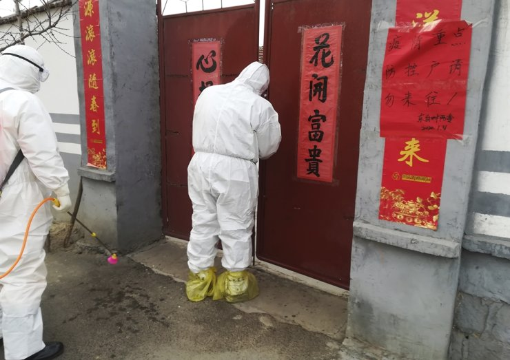 In this Saturday, Feb. 1, 2020, photo, government workers in protective suits visit a family under home quarantine in Zouping in eastern China's Shandong Province. The sign on the right reads: 'Key household for outbreak, family under quarantine, please do not visit.' (Chinatopix via AP)