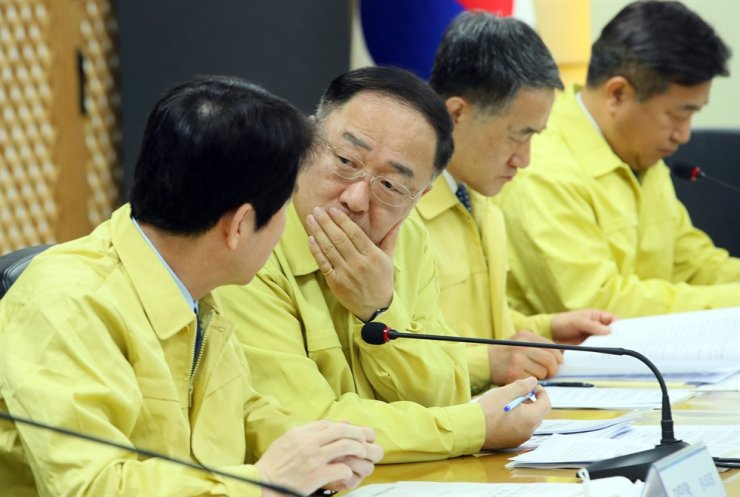 Finance Minister Hong Nam-ki, second from left, converses with the ruling Democratic Party floor leader Lee In-young during a high-level emergency meeting regarding the novel coronavirus at the party's office in Yeouido, Seoul, Feb. 25. Yonhap