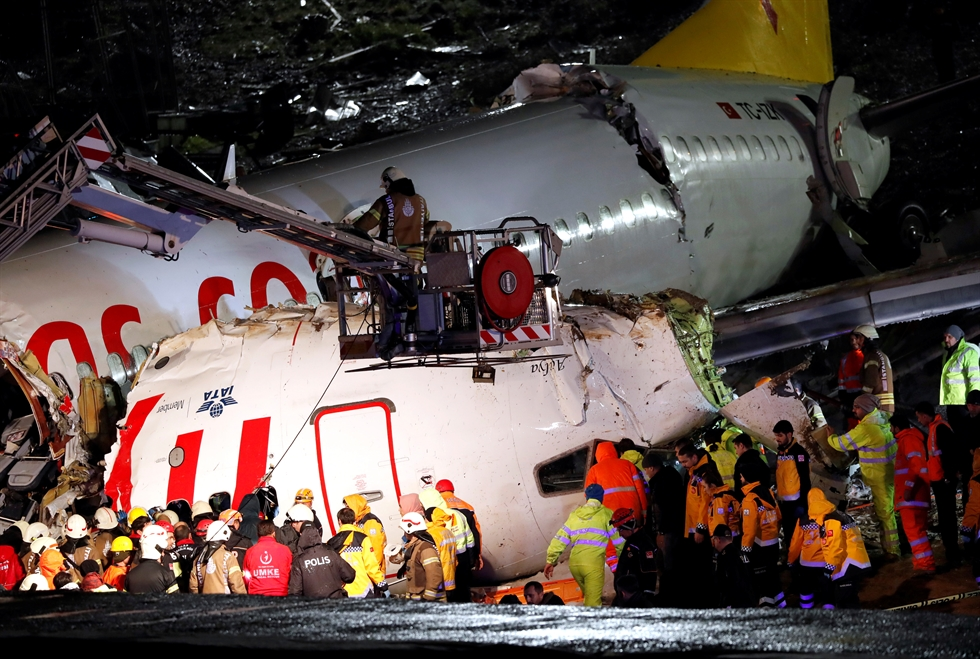 Rescuers work to extract passengers from the crash of a Pegasus Airlines Boeing 737 airplane, after it skidded off the runway upon landing at Sabiha Gokcen airport in Istanbul, Wednesday. /AFP