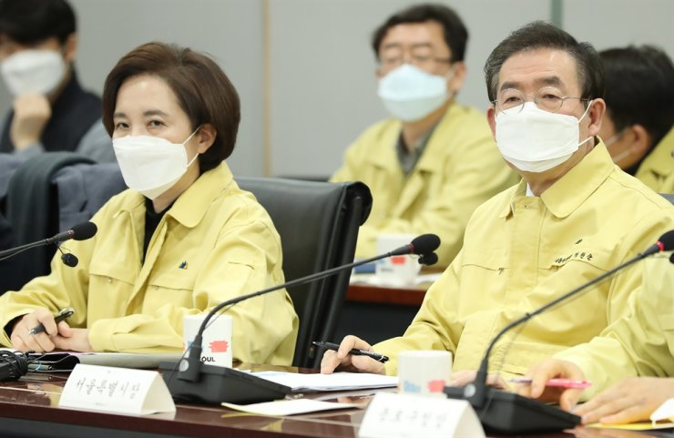 Education Minister Yoo Eun-hae, left, and Seoul Mayor Park Won-soon, attend an emergency meeting to establish a series of measures for managing Chinese students set to return for spring semester next week, at Seoul City Hall, Friday. /Yonhap