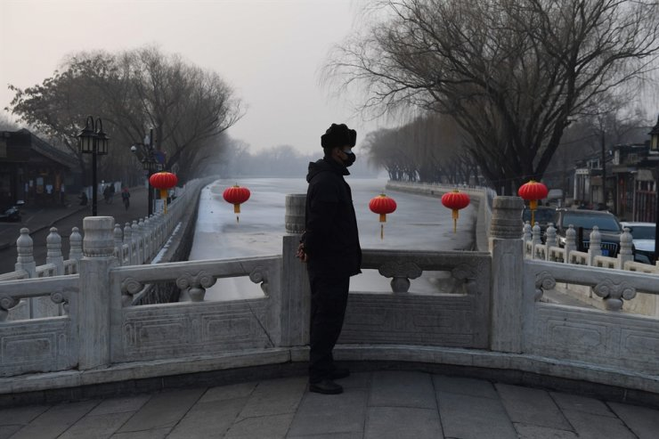 A security guard wears a face mask as he stands on a bridge at the Houhai lake area in Beijing on Feb. 12, 2020. The death toll from the COVID-19 coronavirus epidemic has climbed past 1,300. AFP