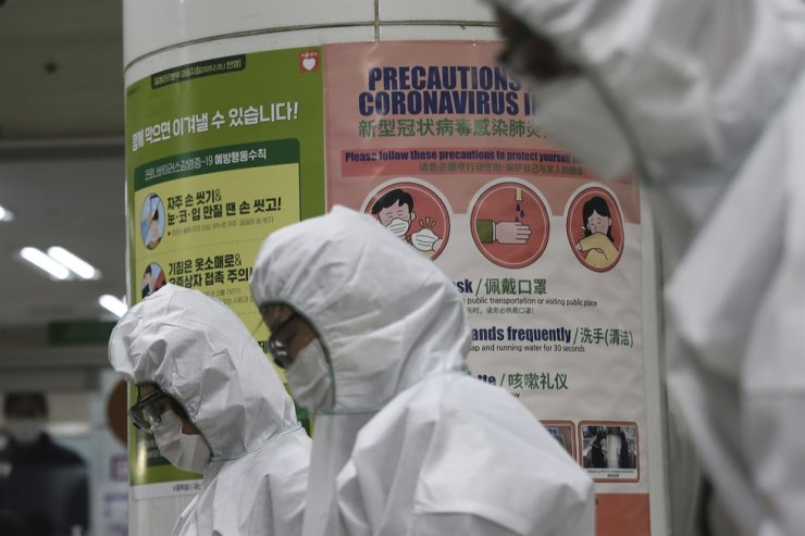 Posters warning about the new coronavirus are displayed as workers wearing protective gears spray disinfectant as a precaution against the coronavirus at a subway station in Seoul, Friday, Feb. 28, 2020. AP