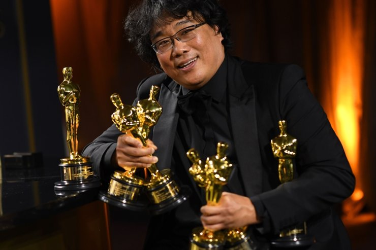 In this file photo South Korean film director Bong Joon-ho poses with his engraved awards as he attends the 92nd Oscars Governors Ball at the Hollywood & Highland Center in Hollywood, California on Feb. 9. / AFP-Yonhap