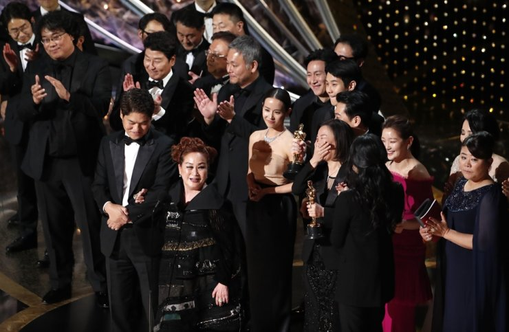 CJ Group Vice Chairwoman Lee Mi-kyung, second from left in the front line, smiles after 'Parasite' won the Oscar for best picture at the 92nd Academy Awards in Hollywood, Los Angeles, California. Sunday (local time). / Reuters-Yonhap