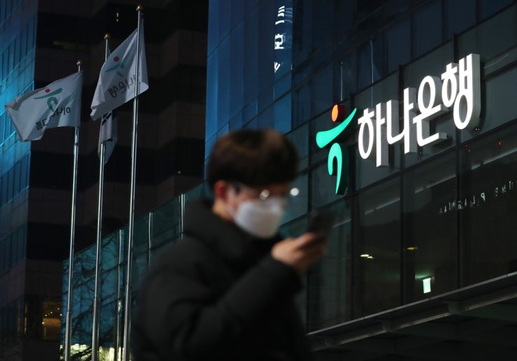 A man wearing a mask passes by the Hana Bank's main branch in downtown Seoul, Sunday. / Yonhap