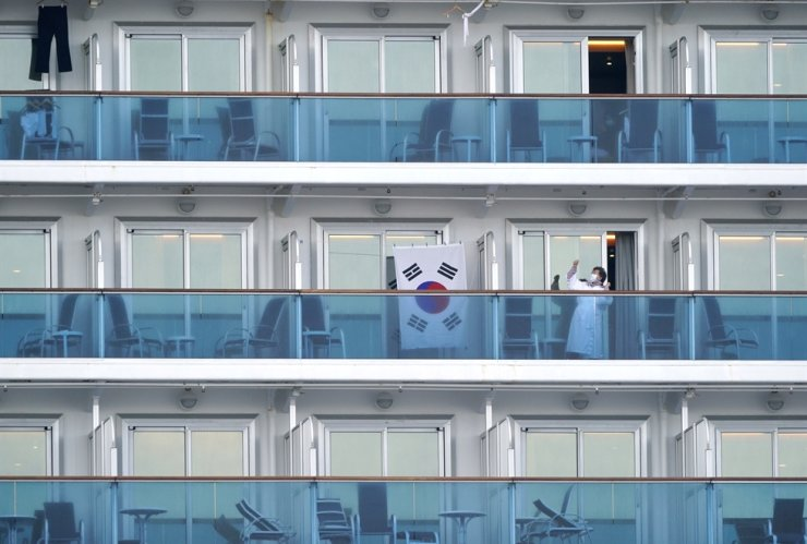 A passenger of the Diamond Princess stretches next to the Korean flag at the Daikoku Pier Cruise Terminal in Yokohama, south of Tokyo, Japan, Feb. 14, 2020. Fourteen Koreans are among the people stuck on the virus-stricken cruise ship. EPA