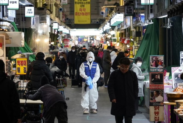 An employee from a disinfection service company sanitizes the floor of a traditional market in Seoul, Monday. Reuters