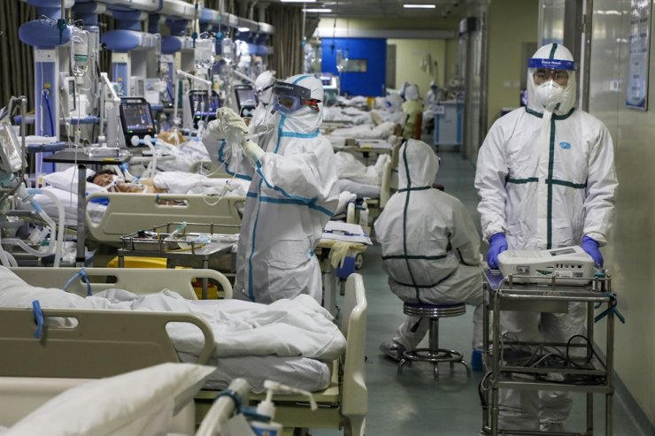 In this Thursday, Feb. 6, 2020, photo, medical workers treat patients in the isolated intensive care unit at a hospital in Wuhan in central China's Hubei province. China's virus death toll have surpassed the number of fatalities in the 2002-03 SARS epidemic, but fewer new cases were reported in a possible sign its spread might be slowing as other nations stepped up efforts to block the disease. AP