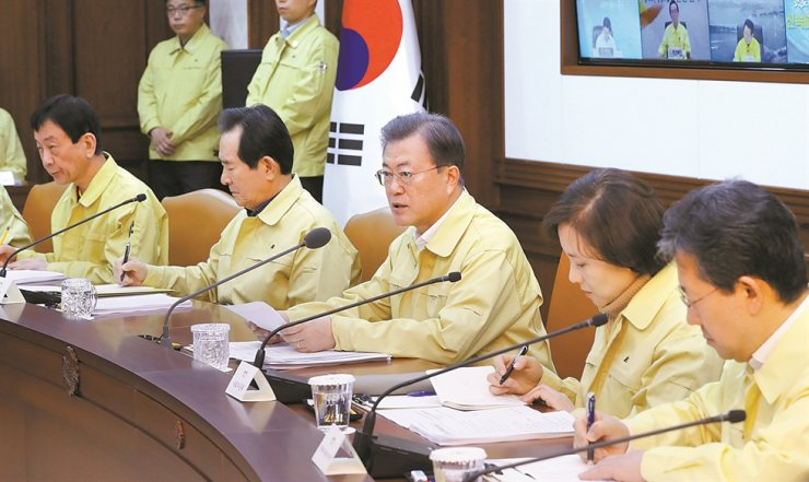 President Moon Jae-in speaks at an inter-agency meeting on COVID-19 at the Government Complex Seoul, Sunday, amid confirmation of hundreds of additional cases of the new coronavirus over the weekend. Moon said the government has decided to raise the alert level for the virus to its 'highest' as the country is being 'confronted by a grave watershed.' / Yonhap