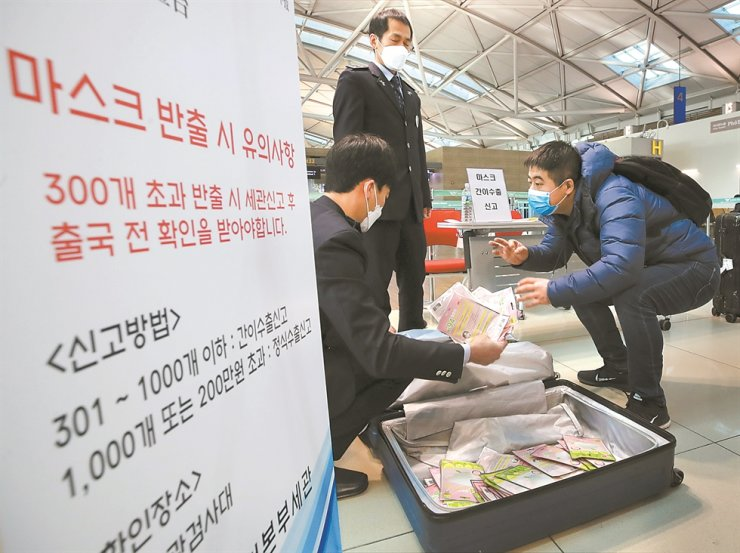 Customs officers check a suitcase of a Chinese tourist at Incheon International Airport, Wednesday, to count how many facial masks he is taking to his home country. Under emergency measures drawn up by the government amid skyrocketing demand for masks due to the coronavirus outbreak, those who take more than 300 masks out of the country should go through a customs declaration. / Yonhap