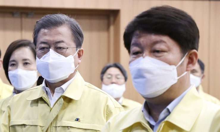 President Moon Jae-in, second from left, and Daegu Mayor Kwon Young-jin pledge allegiance to the national flag at the Daegu City Office before an emergency meeting about the viral coronavirus in the country, Feb. 25. Yonhap