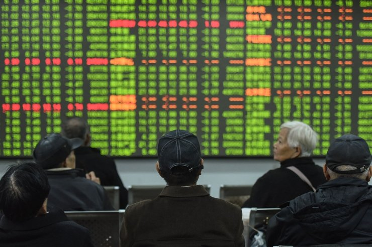 Investors look at a screen showing stock market movements at a securities company in Hangzhou in China's eastern Zhejiang province on February 3, 2020. AP