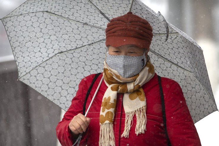 A woman in a face mask walks along a shopping street as snow falls in Beijing Wednesday. Deaths from the new coronavirus rose to 490 in mainland China as new cases on a Japanese cruise ship, in Hong Kong and other places showed the increasing spread of the disease and renewed attention on containing it. (AP Photo/Mark Schiefelbein)