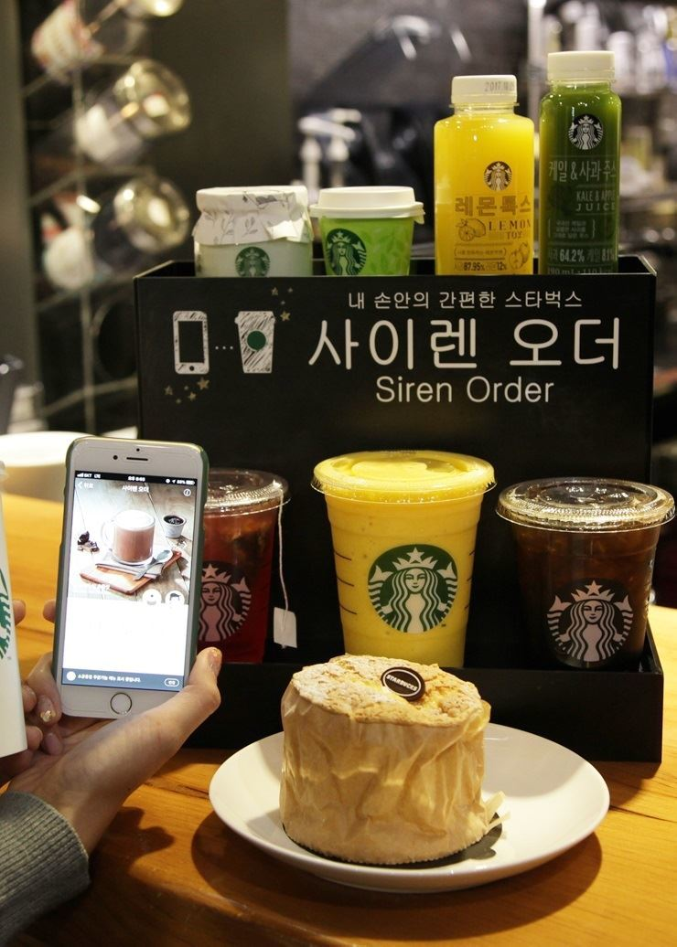A customer orders drinks and a muffin with the 'siren order' system on her mobile application at a Starbucks coffee shop in Seoul in this 2018 file photo. / Yonhap