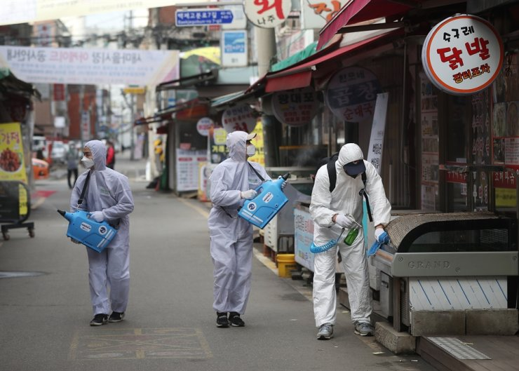 Workers in protective suits spray disinfectants at a traditional market in southern Seoul, Wednesday. Yonhap