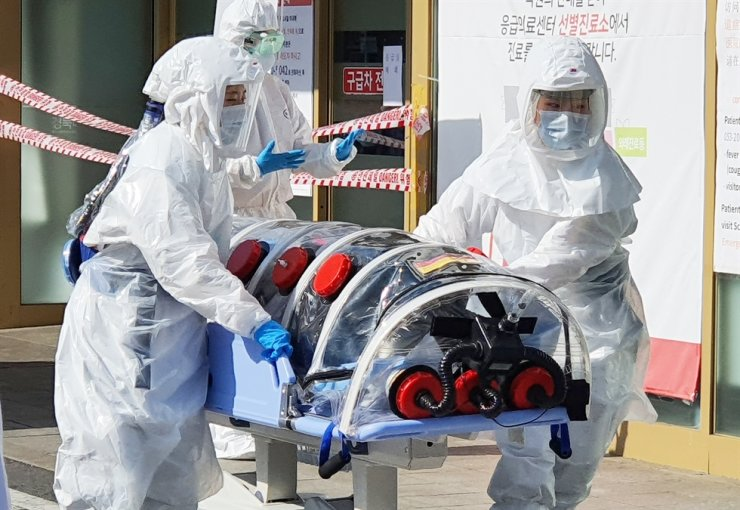 Quarantine officials move a patient suspected of having been infected with the coronavirus to Kyungpook National University Hospital in Daegu, Wednesday, amid growing concerns over the spread of the contagious virus in local communities despite the government tightening quarantine measures. / Yonhap