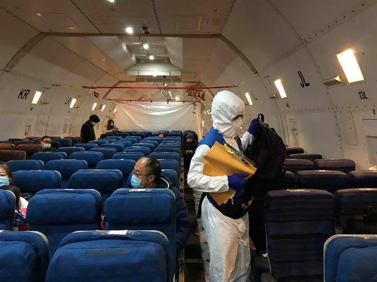Staff from the U.S. embassy walk in a cargo plane, chartered by the U.S. State Department to evacuate Americans and Canadians from China due to the outbreak of a novel coronavirus, during the boarding process at Wuhan Tianhe International Airport, Feb. 7. Reuters