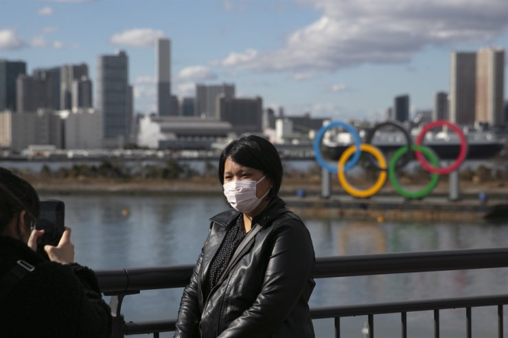 In this Jan. 29, 2020, file photo, a tourist wearing a mask poses for a photo with the Olympic rings in the background, at Tokyo's Odaiba district. / AP-Yonhap