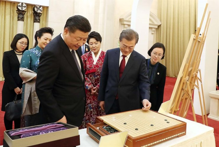 President Moon Jae-in and Chinese President Xi Jinping look at a go board which Xi offered Moon as a present during their 2017 summit in Beijing. Courtesy of Cheong Wa Dae