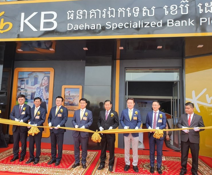 KB Kookmin Card CEO Lee Dong-cheol, fourth from left, cuts a ribbon with other Korean and Cambodian financial authority officials at the opening ceremony for the card firm's branch in Phnom Penh's district of Sen Sok, Monday. / Courtesy of KB Kookmin Card