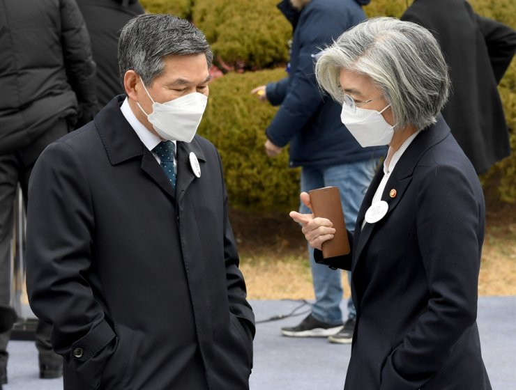 Foreign Minister Kang Kyung-wha, right, and Defense Minister Jeong Kyeong-doo, both wearing masks, talk to each other during a ceremony to mark the 1919 March 1 Independence Movement at Paiwha Girls' High School in Jongno-gu, Seoul. Yonhap