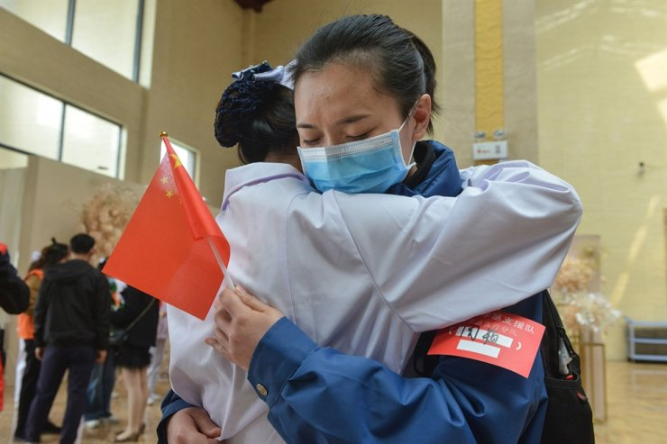 Figure1 A local medical staff member, left, hugs a member of a medical assistance team from Chongqing on March 23, before the team departed after helping with the COVID-19 recovery effort at Yunmeng county in Xiaogan city in China's central Hubei province. AFP