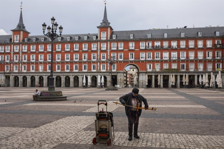 Spanish cartoonist Maria del Rosario 'Chary' closes his stall after been told by local police to leave Mayor square in downtown Madrid, Spain, Sunday, March 15, 2020. Spain awoke to its first day of a nationwide quarantine on Sunday after the government declared a two-week state of emergency. AP