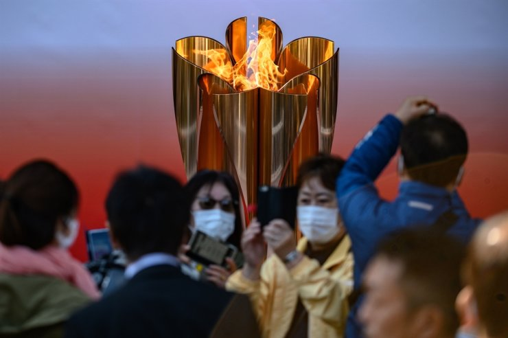 People wearing face masks take pictures in front of the Tokyo 2020 Olympic flame, which is displayed outside Sendai railway station, Miyagi prefecture, on March 21, 2020, after arriving from Greece. AFP