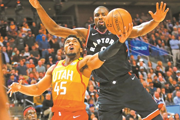Toronto Raptors center Serge Ibaka, rear, defends against Utah Jazz guard Donovan Mitchell who goes to the basket in the second half during an NBA basketball game Monday in Salt Lake City. / AP-Yonhap
