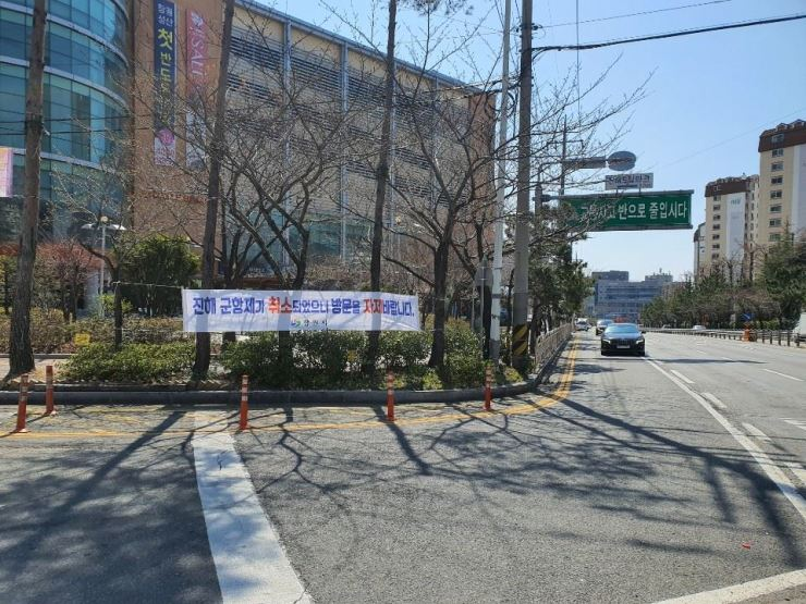 A banner hangs in Jinhae County of Changwon City, Tuesday, calling on people to refrain from visiting the area as cherry blossom season is about to begin. / Courtesy of Changwon City