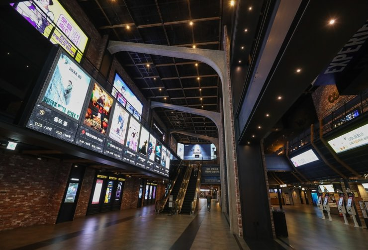A man walks at the mostly empty movie theater in Seoul, March 18. Yonhap
