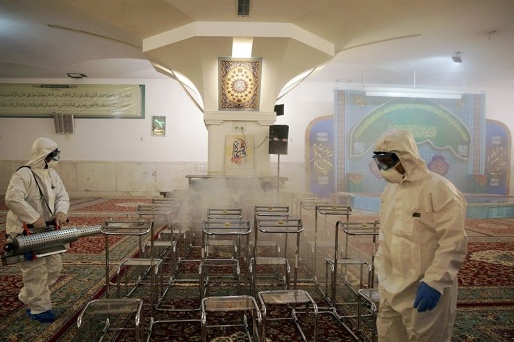 Members of a medical team spray disinfectant to sanitize indoor place of Imam Reza's holy shrine, following the coronavirus outbreak, in Mashhad, Iran February 27, 2020. Picture taken February 27, 2020. WANA (West Asia News Agency) via REUTERS