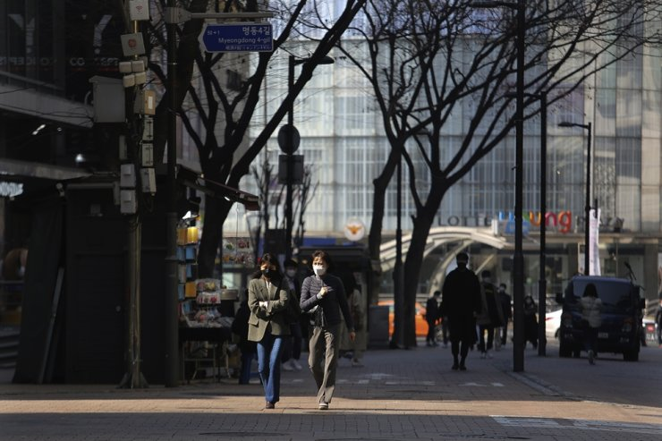 Women wearing face masks walk down a shopping street in Seoul, South Korea, Sunday, March 8, 2020. AP