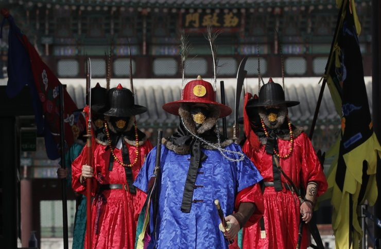 Officials wearing traditional guard uniforms and protective face masks at the Gyeongbok Palace in Seoul, Feb. 29. AP