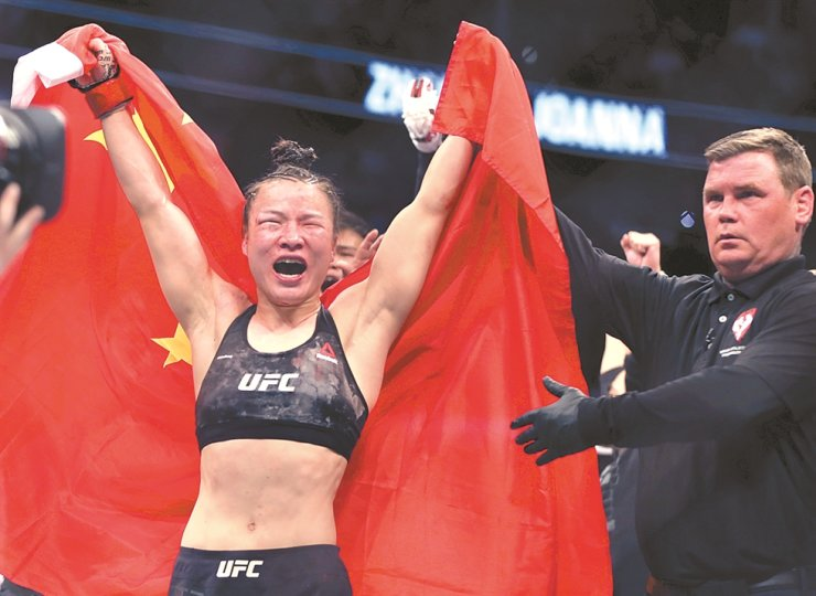Zhang Weili, left, celebrates her win by decision over Joanna Jedrzejczyk in the women's strawweight championship mixed martial arts bout at UFC 248 on Saturday in Las Vegas. / AP-Yonhap