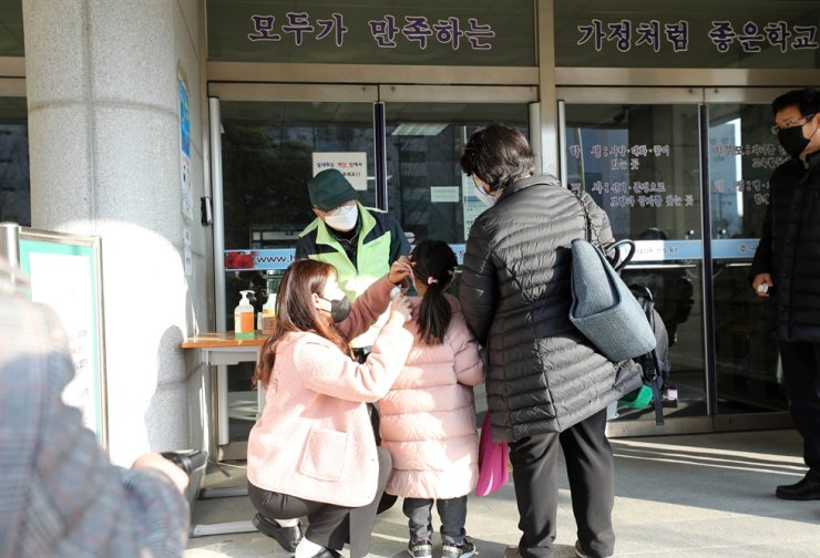 A pupil has her temperature taken by a teacher during an emergency care service at an elementary school in Goyang, Gyeonggi Province, Monday. The service has been implemented as a part of support for working parents as schools in the country have delayed the commencement of spring semester over concerns over the spread of COVID-19.