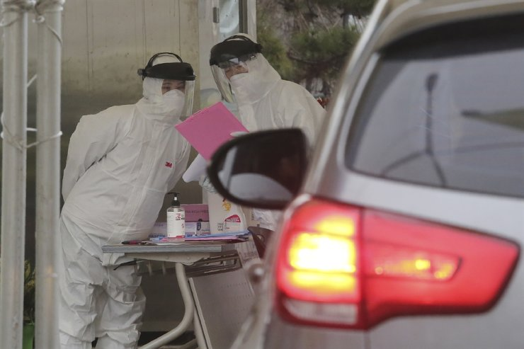 Medical staffs wearing protective suites work to take samples from drivers with suspected symptoms of the coronavirus at a 'drive-through' virus test facility in Goyang, South Korea, Sunday, March 1, 2020. (AP Photo/Ahn Young-joon)