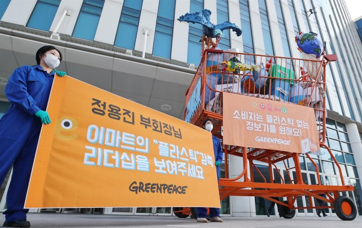 Greenpeace activists protesting single-use plastic bags hold a banner calling for Shinsegae Group Vice Chairman Chung Yong-jin to make efforts to reduce plastic packaging waste in front of E-Mart's headquarters in Seoul, Thursday. / Yonhap