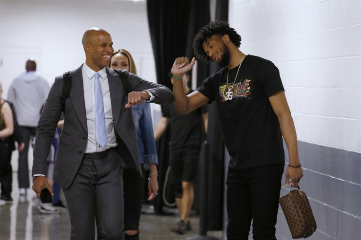 Former NBA player Richard Jefferson, now a television commentator, left, bumps elbows with Sacramento Kings forward Marvin Bagley III as they leave the arena after the Kings' NBA basketball game against the New Orleans Pelicans was postponed in Sacramento, Calif., Wednesday. The postponement was due to what the league said was an 'abundance of caution,' because official Courtney Kirkland, who was scheduled to work the game, had worked the Utah Jazz game earlier in the week. A player for the Jazz tested positive for the coronavirus. / AP-Yonhap