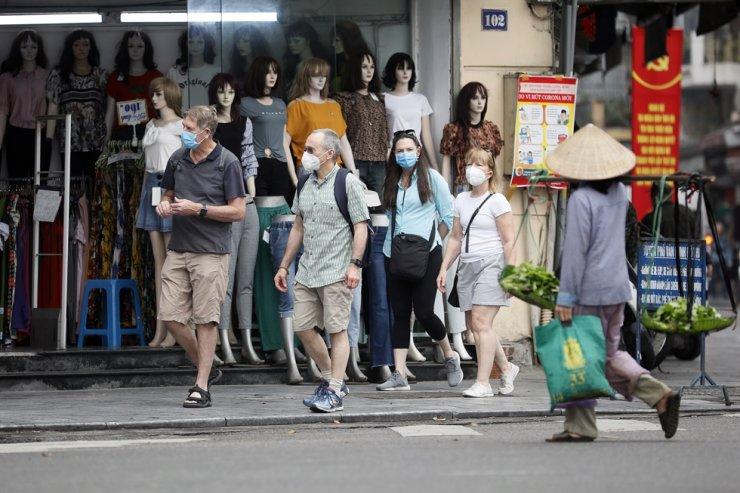 Foreign tourists wearing face masks walk in Hanoi, Vietnam, March 12, 2020. EPA