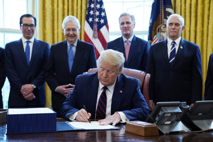U.S. President Donald Trump signs the coronavirus stimulus relief package, at the White House, Friday, March 27, 2020, in Washington, as from left, Treasury Secretary Steven Mnuchin, Senate Majority Leader Mitch McConnell of Ky., House Minority Kevin McCarthy of Calif., and Vice President Mike Pence, look on. AP