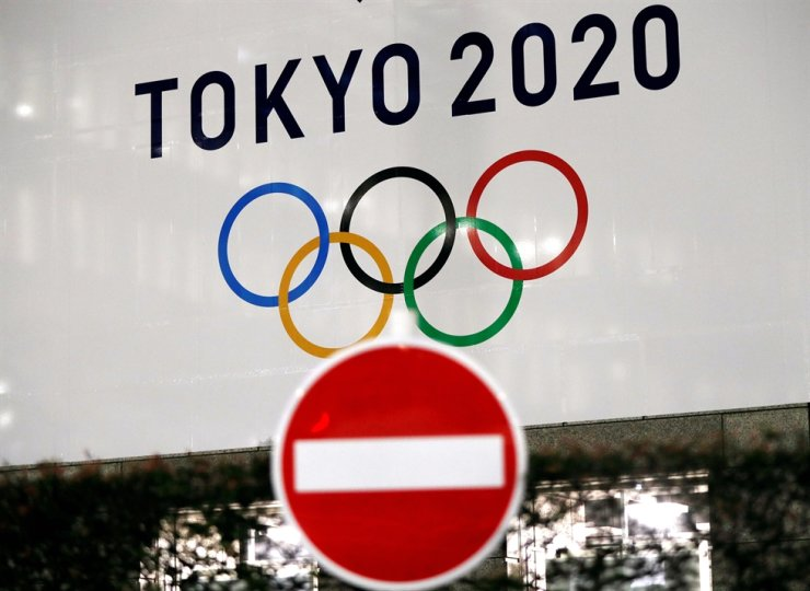 A banner for the Tokyo 2020 Olympics is seen behind a traffic sign in Tokyo, Japan, March 23, 2020. /REUTERS